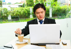 Stirring cofee while working. Inside the cafe that surrounded by glass wall; he is working with his laptop while stirring the coffee. Clean green environment in Royalty Free Stock Image