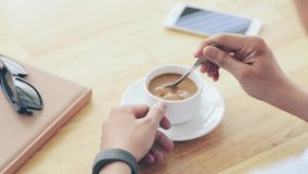 Stirring coffee. Cinemagraph of person mixing sugar in coffee cup stock footage