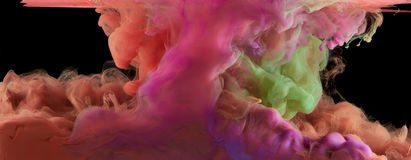 Stirring colors under water. Ink stirring together under water on black background. Colorful Stock Photo