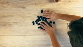 Stirring dominoes on the table during a family game of dominoes. View from above.