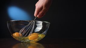 Stirring Eggs in a Glass Bowl with a Whisker. Against a dark blue background. Close-up shot Stock Photos