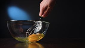 Stirring Eggs in a Glass Bowl with a Whisker. Against a dark blue background. Close-up shot Royalty Free Stock Photography
