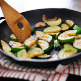 Stirring fried zucchini, in an iron skillet Stock Photo