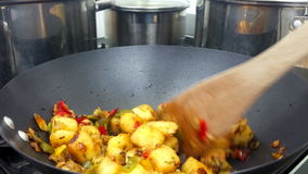Stirring a Mediterranean vegetable mix on a busy stove stock footage