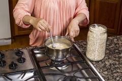 Stirring Oatmeal for Breakfast Stock Images
