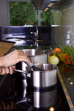 Stirring in the saucepan. A person is cooking in a modern kitchen. She is stirring in the saucepan stock images