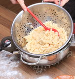 Stirring Spaetzle. Spaetzle in a sieve on top of a pressure cooker are stirred Royalty Free Stock Image