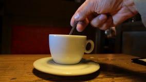 Stirring sugar in the coffee cup. Customer is stirring sugar with teaspoon in the white cup in a dark cafe