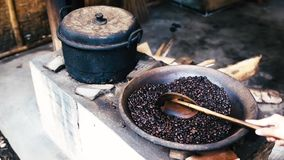 Stirring uncooked coffee beans in frying pan in old traditional way by hand stock footage