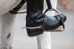 Stirrup and boot. Close up of a black leather boot on stirrup stock photography