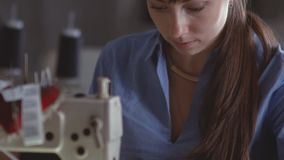 Stitch on the sewing machine. Young dressmaker at work. Slow motion stock video