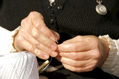 Stitch in time II. Woman carefully threading a needle before beginning sewing stock photo