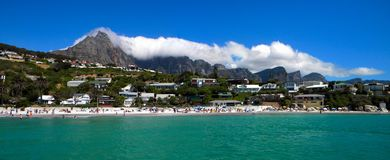Cape Town and coast line, jetty. Far mountain on the blue sky background.Sandy beach and ocean. stock image