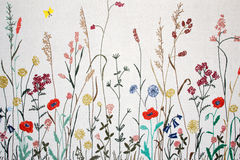 Stitched flowers. Lots of stitched flowers on white linen Royalty Free Stock Photos