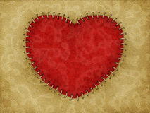 Stitched heart. Red heart made from leather with stitched on brown leather Stock Image