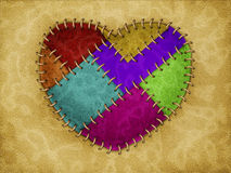 Stitched heart. Colorful heart made from leather with stitched on brown leather Royalty Free Stock Photography