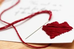 Stitched heart on a card. Stitched heard with red string on a card Royalty Free Stock Image