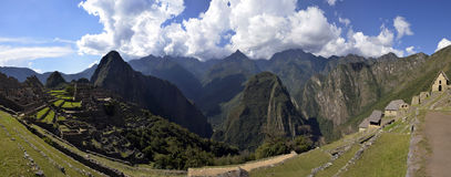 Stitched Panorama of Ruins of Machu Picchu. And Huayna Picchu Peak with Andes Mountain Range and Blue Cloudy Sky in the Background Stock Photo