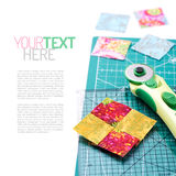 Stitched square pieces of fabric of quilt with rotary knife and. Ruler on craft mat on white surface Stock Photos