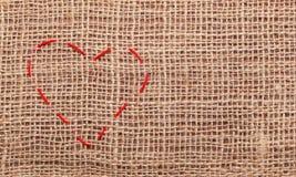 Stitches of heart shape on burlap background Royalty Free Stock Photos