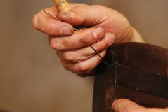 Stitching leather. A skilled worker stitching leather on a horse saddle Royalty Free Stock Images