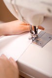 Stitching machine. Working on stitching machine with arms Royalty Free Stock Images