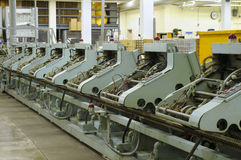 Stitching machines. Row of stitching machines for binding booklets in a publishing house Stock Photography