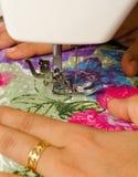 Stitching on sewing machine. A lady is stitching on sewing machine. A beautiful printed cloth is getting stitched stock photo