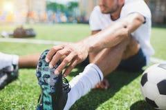 Stivale di calcio della tenuta del calciatore mentre sedendosi sul passo Fotografia Stock Libera da Diritti