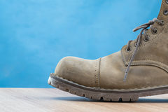 Stivale di cuoio della patina su superficie di legno e su fondo blu fotografie stock libere da diritti
