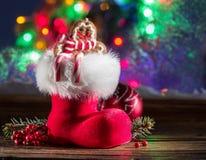 Stivale rosso di Natale alla luce della candela Fotografia Stock