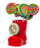 Stivale rosso di Santa Claus, scarpa con le lecca-lecca dolci colorate, candys Stivale di San Nicola con i regali dei presente Fotografie Stock