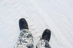 Stivali caldi del lavoro sui precedenti di una strada nevosa immagini stock libere da diritti