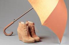 Stivali della pelle scamosciata di Brown sotto un ombrello su un fondo grigio Waterp Fotografie Stock Libere da Diritti