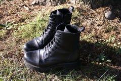 Stivali di combattimento neri su erba Fotografie Stock