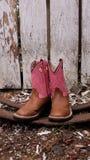 Stivali di cowboy rosa e marroni contro un recinto ruvido immagine stock libera da diritti