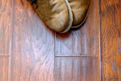 Stivali di cuoio consumati su un pavimento di legno duro Fotografia Stock