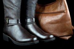 Stivali di cuoio e borsa su fondo nero Fotografia Stock Libera da Diritti