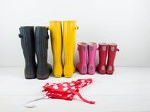 Stivali di gomma con un ombrello contro una parete bianca Fotografie Stock