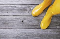 Stivali di gomma gialli sui bordi di legno Fotografie Stock Libere da Diritti