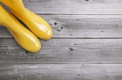 Stivali di gomma gialli sui bordi di legno Fotografia Stock