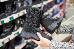 Stivali di inverno in mani dei clienti delle donne al deposito Fotografie Stock