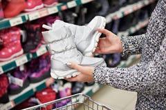 Stivali di inverno in mani dei clienti delle donne al deposito Fotografie Stock Libere da Diritti
