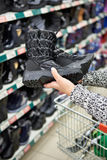 Stivali di inverno in mani dei clienti delle donne al deposito Fotografia Stock