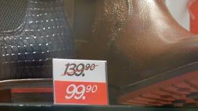 Stivali di lusso di cuoio costosi nel deposito della vetrina della scarpa accanto alla fine dell'etichetta di prezzo di sconto su archivi video