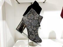 Stivali di modo del ` s delle donne nel deposito sullo scaffale Fotografia Stock