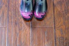 Stivali di pioggia su un pavimento di legno Fotografia Stock Libera da Diritti
