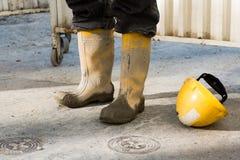 Stivali e casco fangosi di Workmans fotografia stock libera da diritti