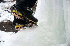 Stivali e ramponi di uno scalatore su ghiaccio su una cascata congelata Fotografia Stock