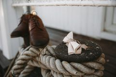 Stivali e sposo della farfalla del legame sulle bitte avvolte nella corda spessa della iuta fotografie stock